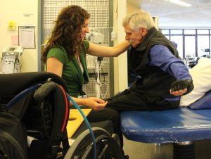 In the foreground, a wheelchair is visible. In the background a man with white hair sits on a therapy mat with his arms extended. A woman in a green shirt is seated facing him with her hand on his shoulder.